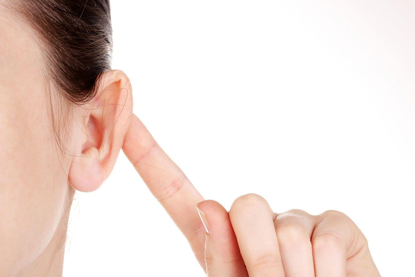 A woman pushes her ear forward with her finger